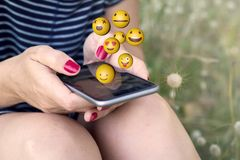 Woman sending emoji smartphone on the grass. Sitting woman sending emoji with smartphone on the grass. All screen graphics are made up royalty free stock image