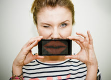 Woman sending kiss on smartphone Stock Photos