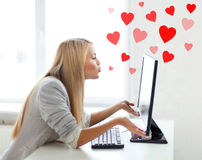 Woman sending kisses with computer monitor Royalty Free Stock Image