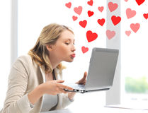 Woman sending kisses with laptop computer Stock Image