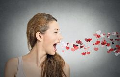 Woman sending kisses, red hearts coming out of open mouth. Side view portrait beautiful woman sending kisses, red hearts coming out of open mouth, isolated grey royalty free stock photos