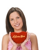 Woman sending a love message. Beautiful young brunette holding a read plush shape with a love message on it Royalty Free Stock Photo