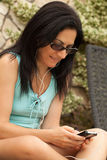Woman Sending Messages From Smartphone. Young Caucasian brunette woman sitting on sunbed outside in the garden and sending messages from smartphone Stock Images
