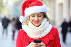 Woman sending phone text on christmas in the street stock photography