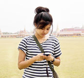 Woman sending / receiving a text message. / email on her mobile / cellular phone Stock Image