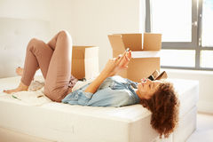 Woman Sending Text Message Having Moved Into New Home Royalty Free Stock Photo