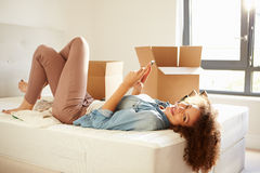 Woman Sending Text Message Having Moved Into New Home Stock Photo