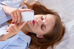 Woman sending text with a mobile phone in bed Royalty Free Stock Image