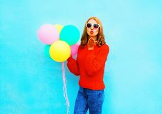 Woman sends an air kiss with colorful balloons. Fashion pretty woman sends an air kiss with colorful balloons on a blue background Royalty Free Stock Photo