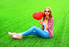 Woman sends an air kiss with red balloon in the shape of a heart. Sits on the grass Royalty Free Stock Photography