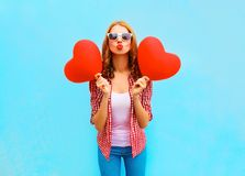 Woman sends an air kiss with a red balloons in the shape of a heart. On blue background Stock Images