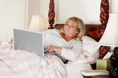 Woman sends e-mail in bed Stock Photography