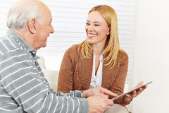 Woman and senior man using tablet Stock Photo