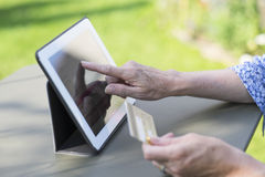 Woman senior using credit card and tablet pc to shop online Royalty Free Stock Photo