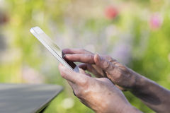 Woman Senior using a mobile phone in garden Royalty Free Stock Photos