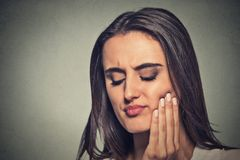 Woman with sensitive toothache crown problem. Closeup portrait young woman with sensitive toothache crown problem about to cry from pain touching red area royalty free stock images
