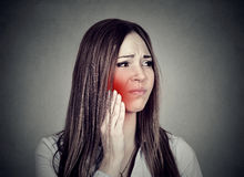 Woman with sensitive toothache suffering from pain touching outside mouth. Young woman with sensitive toothache crown problem suffering from pain touching royalty free stock photography