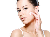 Woman with sensual look applying cream on her face Stock Photos