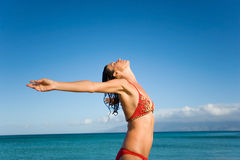 Woman sensual maui beach. Sensual woman in red bikini on beach with arms outstretched feeling serene and free Stock Photography