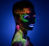 Woman sensual posing in fluorescent paint makeup Royalty Free Stock Images
