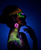 Woman sensual posing in fluorescent paint makeup. Looking at the side. Luminescence paint. Dark blue background with copy space Royalty Free Stock Photos