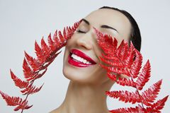 A woman with Sensual red lips and a fern sheet. red lipstick stock image