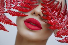 A woman with Sensual red matt lips and a fern sheet stock photos