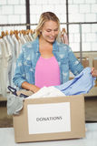 Woman separating clothes from donation box in office Stock Photos