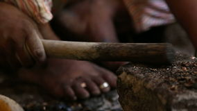 Woman separating crust from cashew nut using mallet. stock video footage
