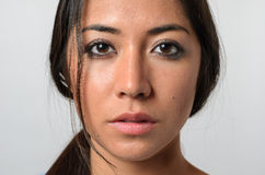 Woman with serious blank stare. One beautiful young woman with stray hair and serious expression and blank stare Stock Image