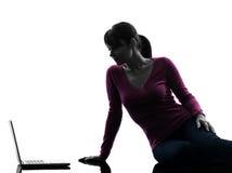 Woman serious computing laptop computer silhouette Stock Photos
