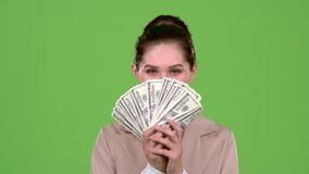 Woman received paper money for a major deal. Green screen. Slow motion. Woman with a serious expression of her face she received paper money for a major stock video