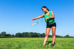 Woman serve with badminton racket and shuttle outside in grass. Colombian woman serve with badminton racket and shuttle outside in grass royalty free stock photography