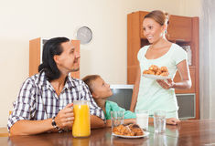 Woman serves croissants  her husband and son Royalty Free Stock Image