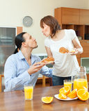 Woman serves croissants and scrambled eggs her beloved man Royalty Free Stock Image