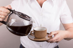Woman serves a cup of coffee stock photography