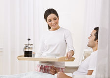 Woman Serving Breakfast Tray to Man. A beautiful young woman serving a breakfast tray to a man lying in bed.  They are smiling happily at one another Royalty Free Stock Image