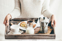 Woman serving breakfast on wooden tray Royalty Free Stock Images