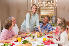 Woman serving christmas dinner to her family Stock Image