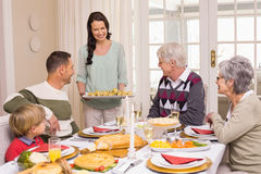 Woman serving christmas dinner to her family Stock Images