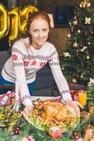 Woman serving christmas table with chicken Royalty Free Stock Photos