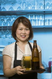 Woman serving cold beer Stock Images