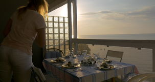 Woman serving dinner on the home balcony stock video footage