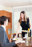 Woman serving dinner for  man at table Royalty Free Stock Image