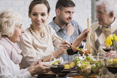 Woman serving dinner to her family Stock Photos