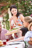 Woman Serving At Family Meal Stock Photo