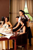 Woman serving food restaurant table Stock Photo