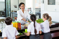 Woman serving food to children Stock Photo