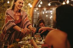 Woman serving food to friends at dinner party stock photo