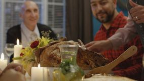 Woman serving holiday turkey for family. Mature woman serving plate with delicious roasted Thanksgiving turkey on table with cheerful family having traditional stock footage